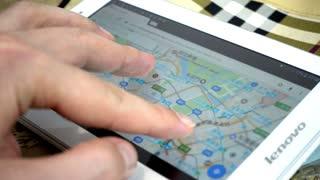 Google Maps On Digital Tablet - Man looking searching Tokyo Japan