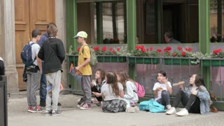Group of Children sitting on a Pavement eating Doner Kebab on a Street