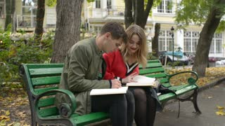 Guy and Girl Students on a Bench in a Park write an Abstract read a Textbook