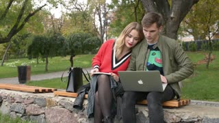 Guy and Girl Students with Laptop on Bench in Park write notes in an Abstract