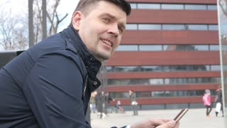 Handsome Man with Mobile Smart Phone browse Network at the City Street, Poland