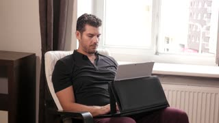 Handsome Man working with Netbook Laptop pc at Home