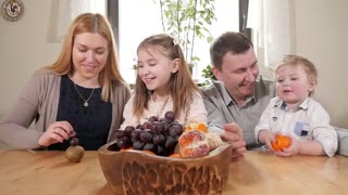 Happy Big Family with Kids at the Kitchen eating juicy Fruits Orange and Grape