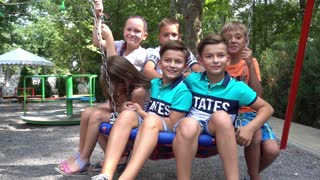 Happy Children on the Swing smile to The Camera on the Playground Summer Day