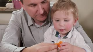 Happy Family Father and Son Kid at Kitchen eating and play juicy Fruits Orange