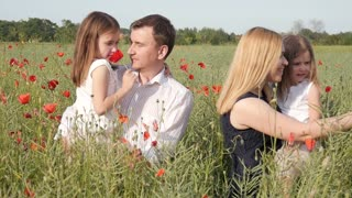 Happy Family in the field of Poppies posing with Red Flowers