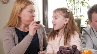 Happy Family Mom and Daughter at Kitchen eating juicy Fruits Orange and Grape