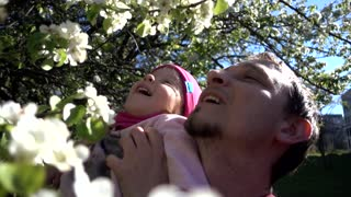 Happy Father And Daughter On The Nature Among The Spring Flowers on Trees