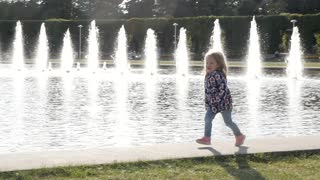 Happy Little Girl Kid running around the Fountain in a Park - Summer Day