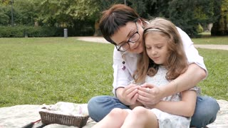 Happy Mother and Daughter gently hug sitting on a Blanket at Park Picnic