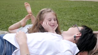 Happy Mother and Daughter hugging lying on Blanket at Park Picnic
