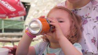 Happy smiling Child Girl drink Orange Soda Fanta sit with Mom on a Food Festival