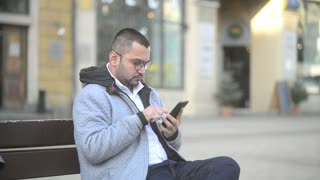Indian Man Chatting Browse Social Network With Mobile Phone At the Street