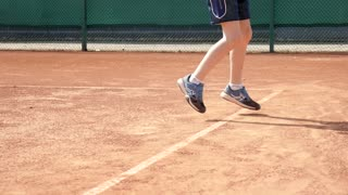 Kid Boy does exercises before playing Tennis on a Cort