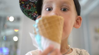 KId Boy eats Ice cream Cone, licks it with Tongue