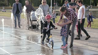 Kid ride a Bicycle on a Water Fountain Splash