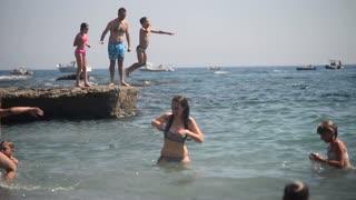 Liguria Italy sea Shore Beach and Rocks - People sunbathe, relax and Swim