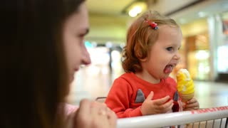 Little child girl eating an Ice Cream Gelato Sour Taste with Mom in Grocery Mall