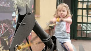 Little Child Girl ride a Plastic Horse in a Yard - Summer Day