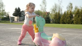 Little child Girl ride and play with Toy Car on the Playground in the Park - Day