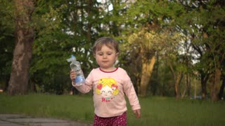 Little Child Walking in Summer Park with bottle of Water