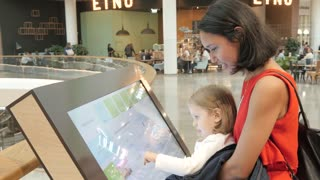 Little Girl Child play with Digital Screen in a Mall