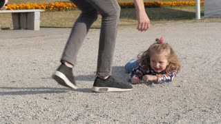 Little Girl fell down hit the Ground and Mother getting up her Daughter on Legs