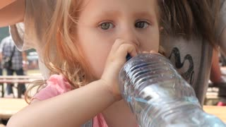 Little Girl Kid drinking Water from a Plastic Bottle on a Street Food Festival
