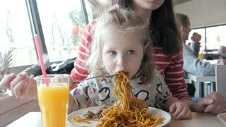 Little Girl Kid eating Pasta Spaghetti with Mother at the Cafe Table