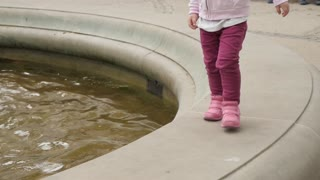 Little Girl walking around the Fountain in a Park - legs only