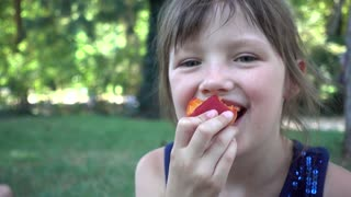 Little Girl With No Front Baby Tooth eating Peach in a Park