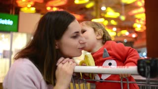 Little kid Daughter kisses Mom sitting in grocery Cart in Supermarket Mall