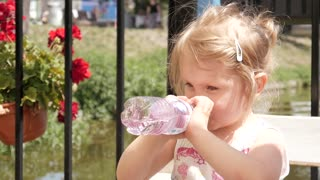 Little Kid Girl Funny Drinking A Clean Water From A Plastic Bottle In Green Park
