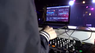 Male Dj Is Performing His Set, people dancing In The Night Club