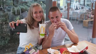 Man and Girl Lovers make Selfie Photo via Mobile Phone in Fast Food Mcdonalds
