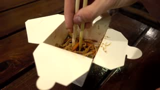 Man eating Chinese Noodles with Chicken and Vegetables with Сhopsticks