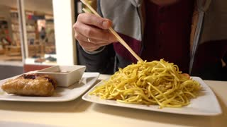 Man Eating Chinese Noodles With Vegetables With Сhopsticks, Fast Food Restaurant