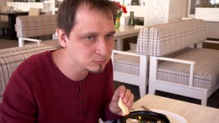Man Eating Lunch with Vegetable Salad, Cheese and Eggs in Restaurant