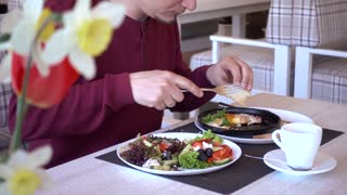 Man Eating Traditional Breakfast With Fried Eggs, Toast and Salad