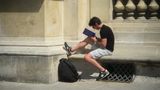 Man reading the Book sitting on the street in city Paris - Day
