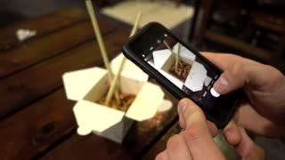 Man taking Photo of Chinese Noodles with Mobile Phone in Restaurant Fast Food