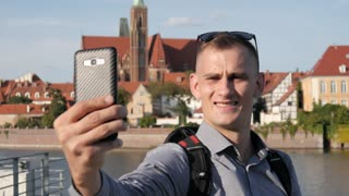 Man Tourist use Mobile Smart Phone to make Selfie Photo, traveling Europe Poland