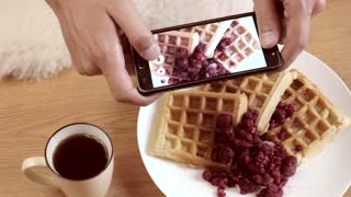 Man use Mobile Smart Phone to make Photo of the Plate with Waffles and Berries