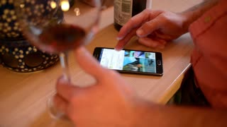 Man use Smartphone browse network and drink a Glass of Wine