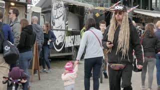 Many People on a Food Festival walking along the Food-trucks