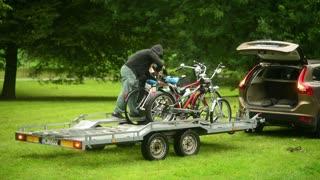 Men attach bikes to a car trailer