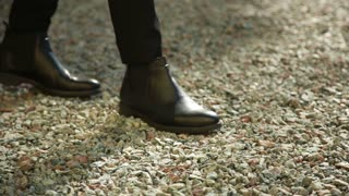 Men's Legs are walking in black Shoes along the Gravel Road