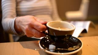 Middle aged Woman Brunette reading a Magazine in a cozy Cafe and a Cup of Coffee