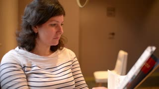 Middle aged Woman Brunette reading a Magazine in a cozy Cafe