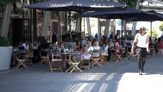 Milan business city center - people eating at cafe tables - Piazza Gae Aulenti